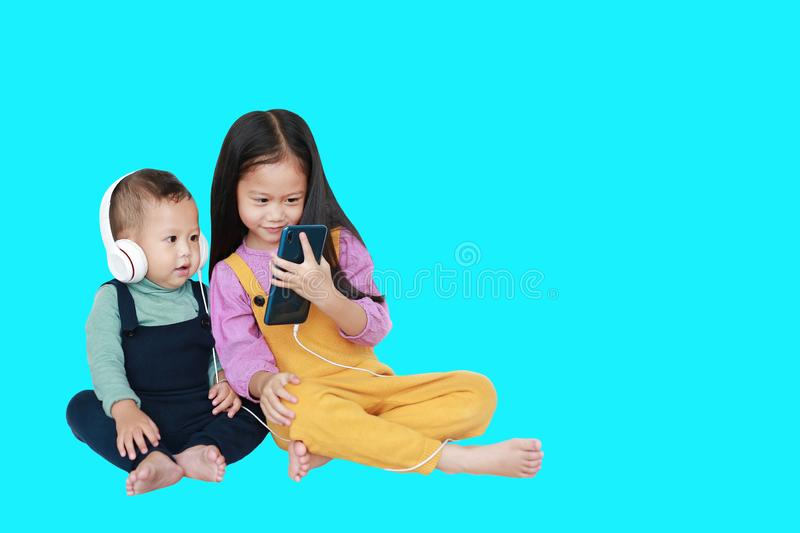 Adorable Asian older sister and little brother sharing to enjoys listening music with headphones by smartphone isolated over cyan. Background with copt space royalty free stock photo