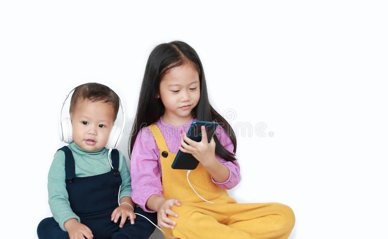 Adorable Asian older sister and little brother sharing to enjoys listening music with headphones by smartphone isolated over white. Background. Sharing concept stock photos
