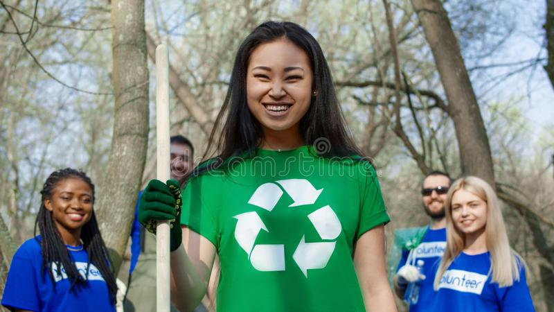 Smiling girl with group of volunteers. Adorable Asian women standing with smiling multiethnic friends in shirts of volunteers working in team in forest royalty free stock image