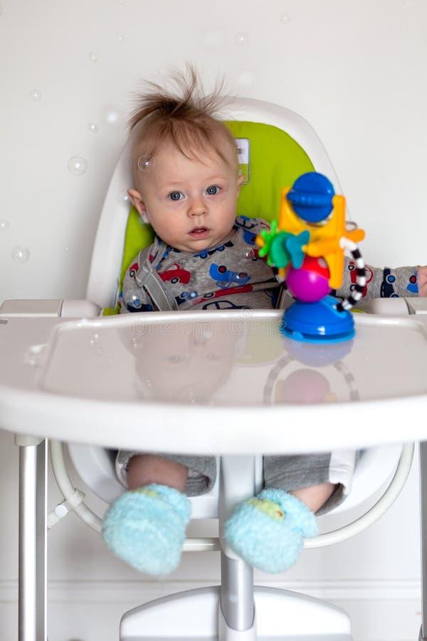 Adorable baby boy in a highchair royalty free stock photos
