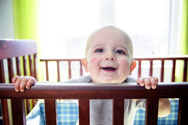 Adorable baby boy in his crib. An Adorable baby boy in his crib royalty free stock images