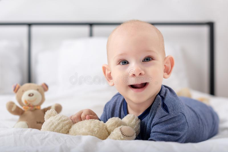 Adorable baby boy laughing and playing with toy bears on a bed. Newborn child relaxing in bed. Family morning at home stock image