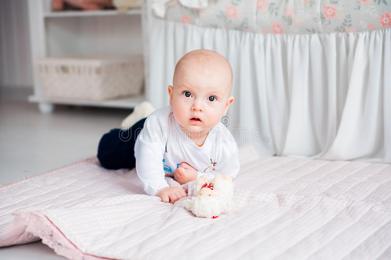 Adorable baby boy laying on the floor in her nursery and play with toy. Photo of Adorable baby boy laying on the floor in her nursery and play with toy stock photos
