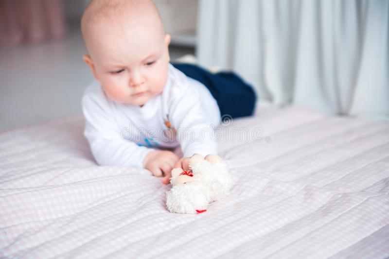 Adorable baby boy laying on the floor in her nursery and play with toy. Photo of Adorable baby boy laying on the floor in her nursery and play with toy royalty free stock photography