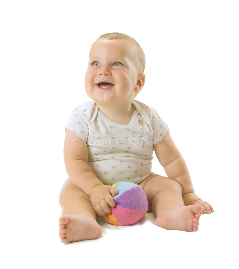 Adorable baby boy siting with colorful ball between his legs, looking up and smiling. Isolated on white background. royalty free stock images
