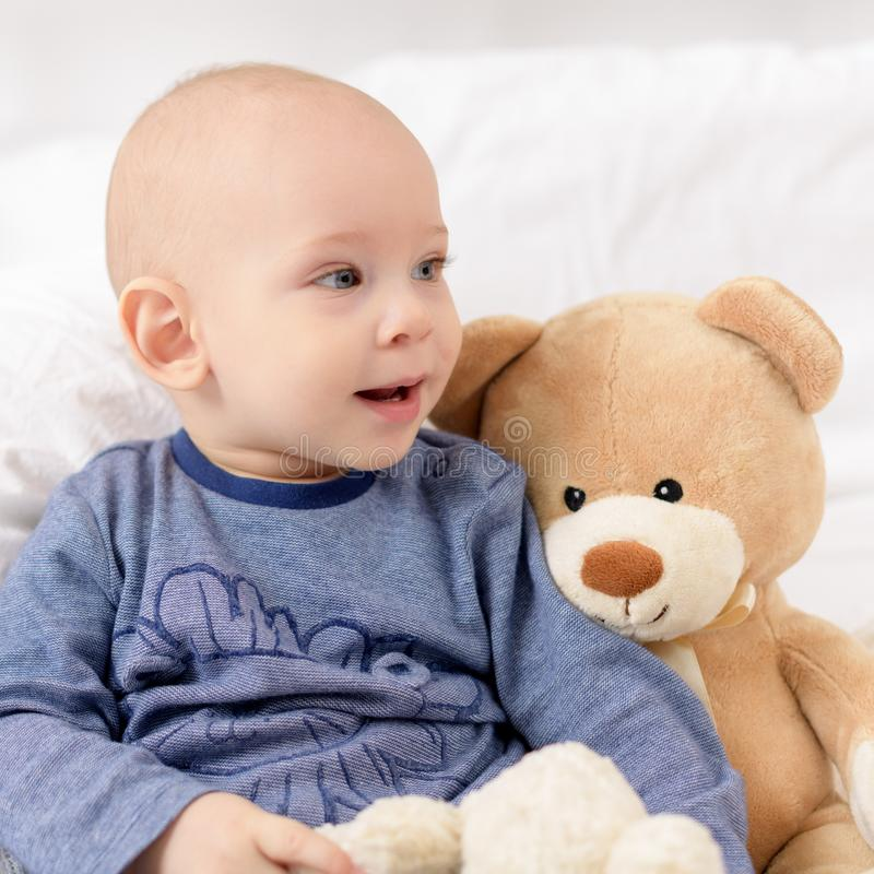Adorable baby boy sitting on a bed, playing with toy bears on a bed. Newborn child relaxing on a bed. Family morning at home stock photo