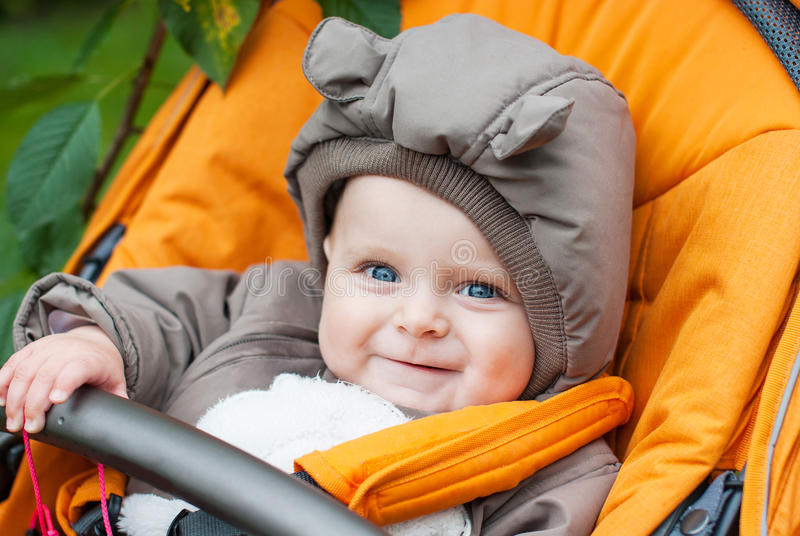 Adorable baby boy in warm winter clothes in stroller. Adorable baby boy in warm winter clothes on stroller royalty free stock image