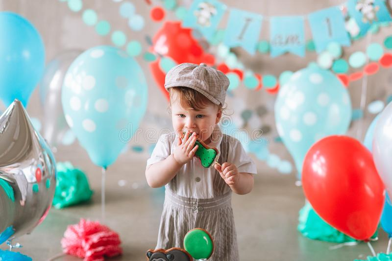 Adorable baby boy wearing suit and hat eating a small birthday cake in decorated studio room royalty free stock image