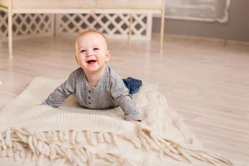 Adorable baby boy in white sunny bedroom. Newborn child. Nursery for young children. Family morning at home. stock photo