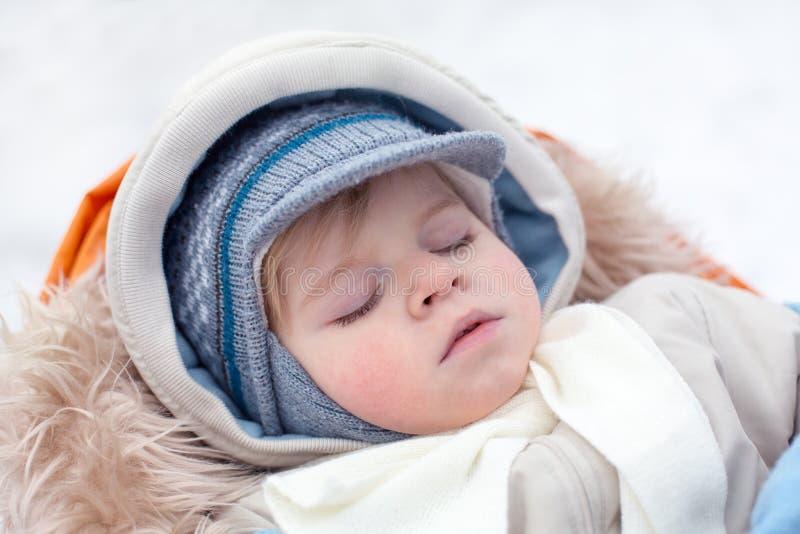 Adorable baby boy in winter clothes sleeping in stroller. Adorable baby boy in winter clothes sleeping in orange stroller outdoor stock image
