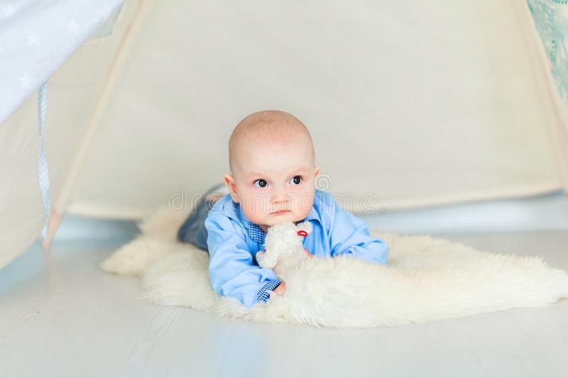 Adorable baby boyl laying on the floor in her nursery under the tent. Photo of Adorable baby boyl laying on the floor in her nursery under the tent royalty free stock photo