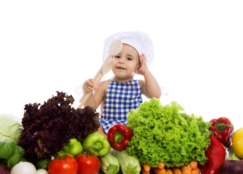 Adorable baby chef with healthy food vegetables and holding scoo stock photos