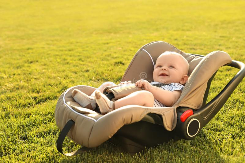 Adorable baby in child safety seat. On green grass stock image