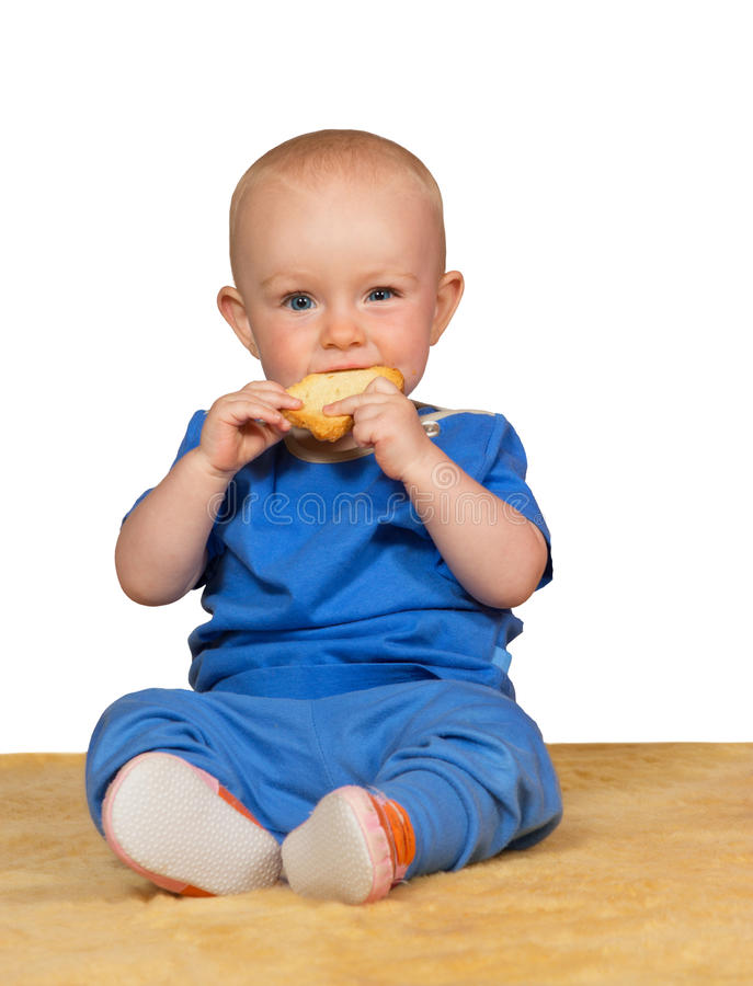 Adorable baby eating a bun royalty free stock images