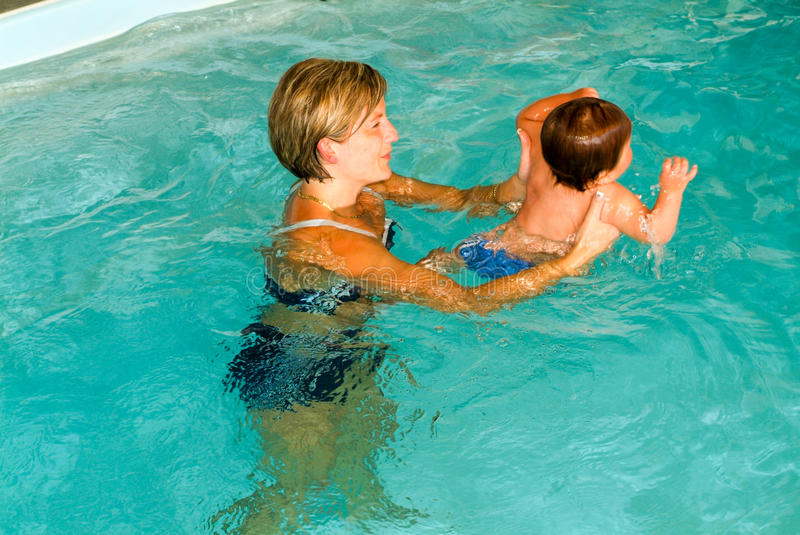 Adorable baby enjoying swimming in a pool with his mother. Lugano, Switzerland - 18 October 2007: Adorable baby enjoying swimming in a pool with his mother stock photos