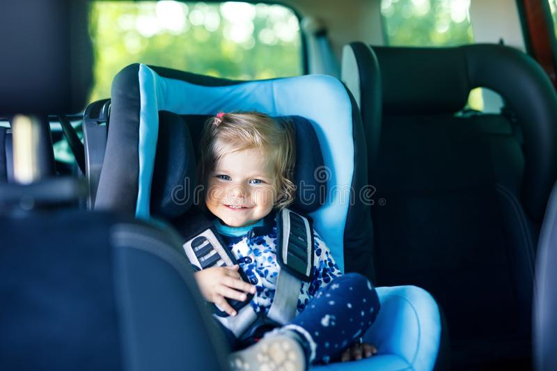Adorable baby girl with blue eyes sitting in car safety seat. Toddler child going on family vacations and jorney. royalty free stock image