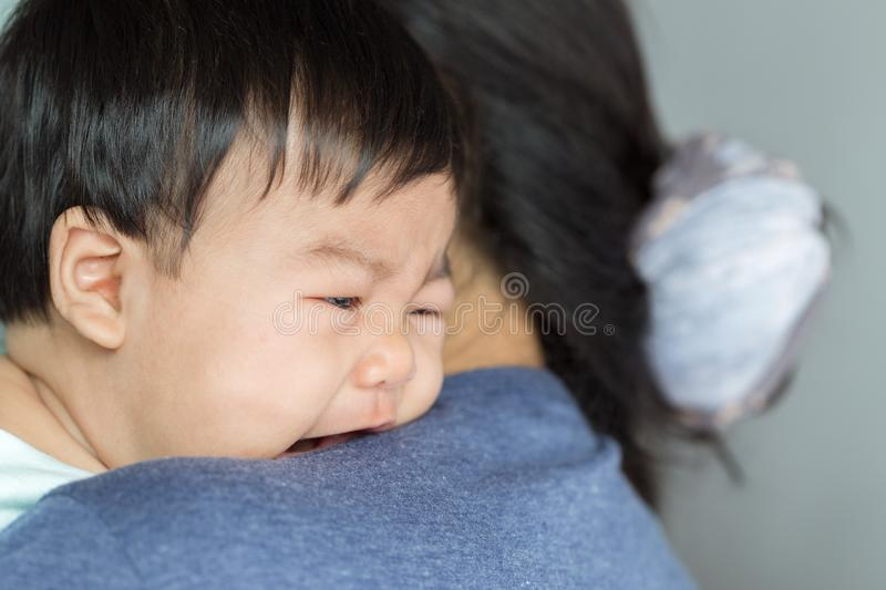 Adorable baby girl cry on mom shoulder. royalty free stock photography