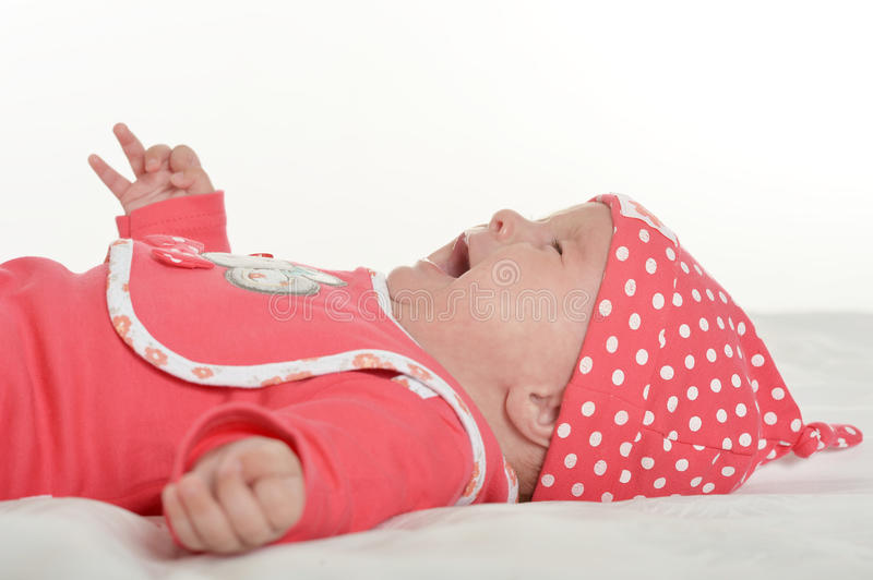 Adorable baby girl crying. Adorable baby girl in cute clothes crying on blanket stock photo