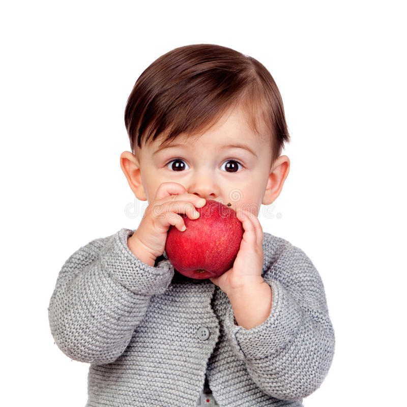 Adorable baby girl eating a red apple stock image