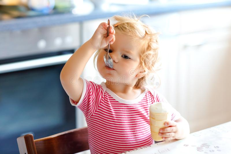 Adorable baby girl eating from spoon sweet ice cream in waffle cone. food, child, feeding and development concept. Cute royalty free stock photography