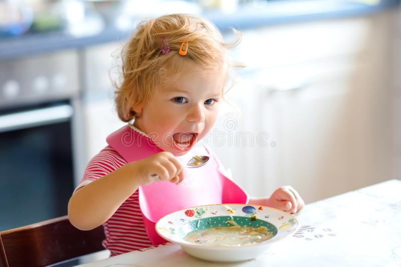 Adorable baby girl eating from spoon vegetable noodle soup. food, child, feeding and development concept. Cute toddler royalty free stock image