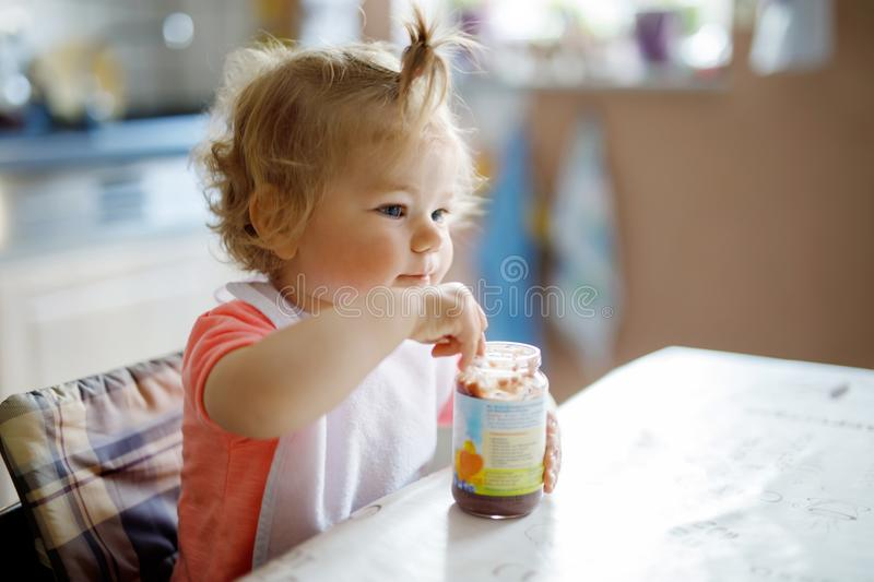 Adorable baby girl eating from spoon vegetables or fruit canned food, child, feeding and development concept. royalty free stock images
