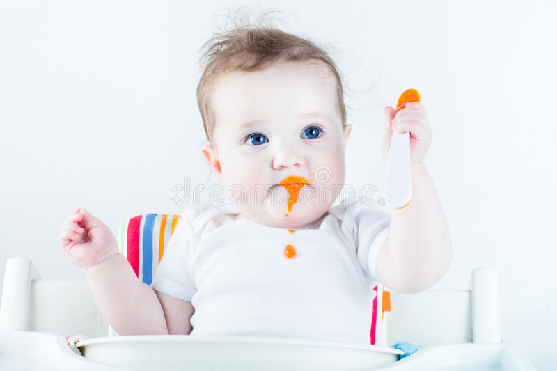 Adorable baby girl eating vegetables for the first time. Adorable little baby girl eating vegetables for the first time royalty free stock image