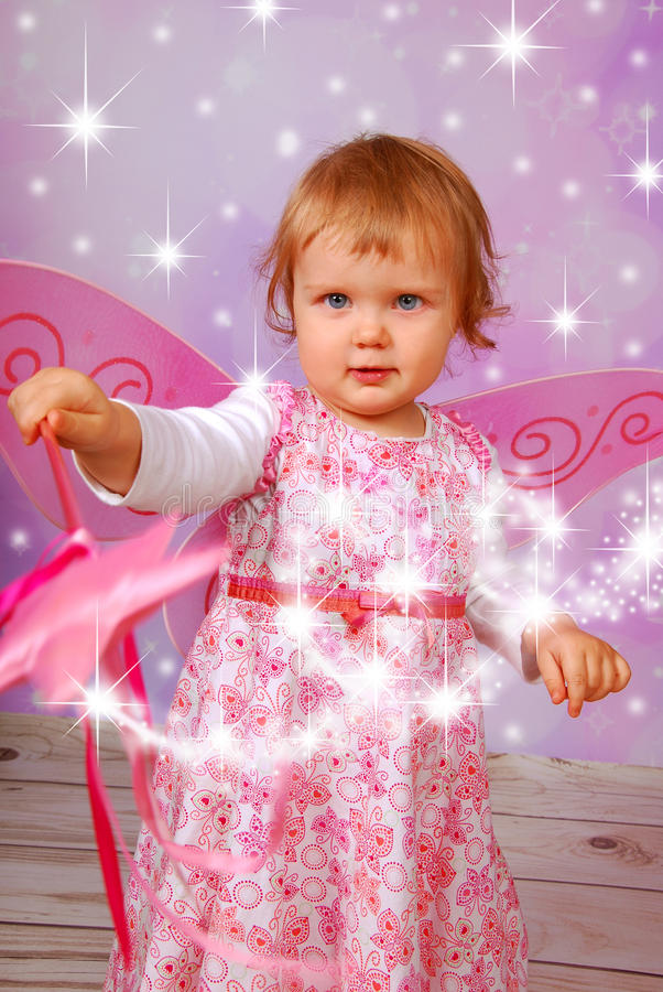 Adorable baby girl with fairy wings and wand royalty free stock image