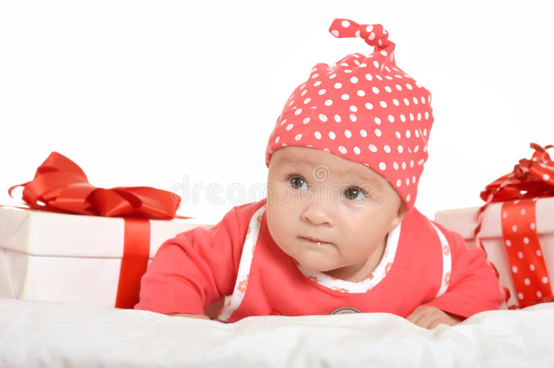 Adorable baby girl with gifts. Adorable baby girl in red clothes with gifts stock photos