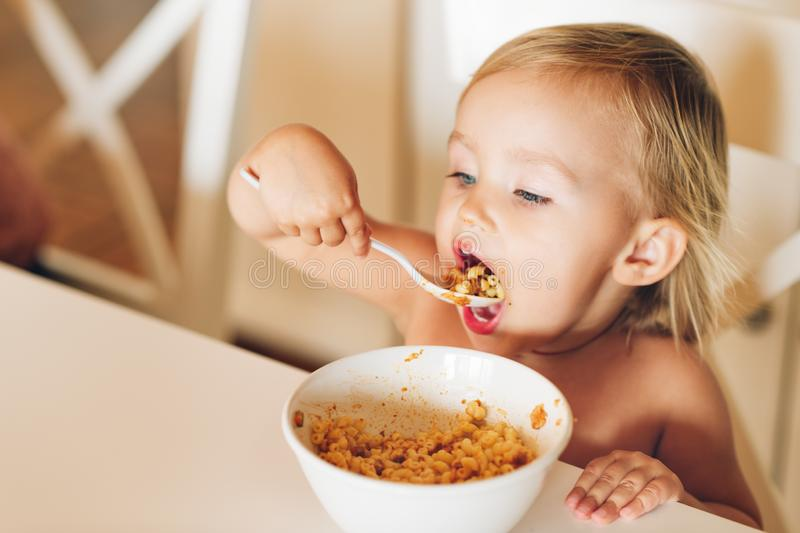 Adorable baby girl with good appetite eats pasta royalty free stock photo