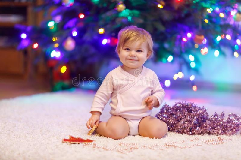 Adorable baby girl holding colorful lights garland in cute hands. Little child in festive clothes decorating Christmas stock photography