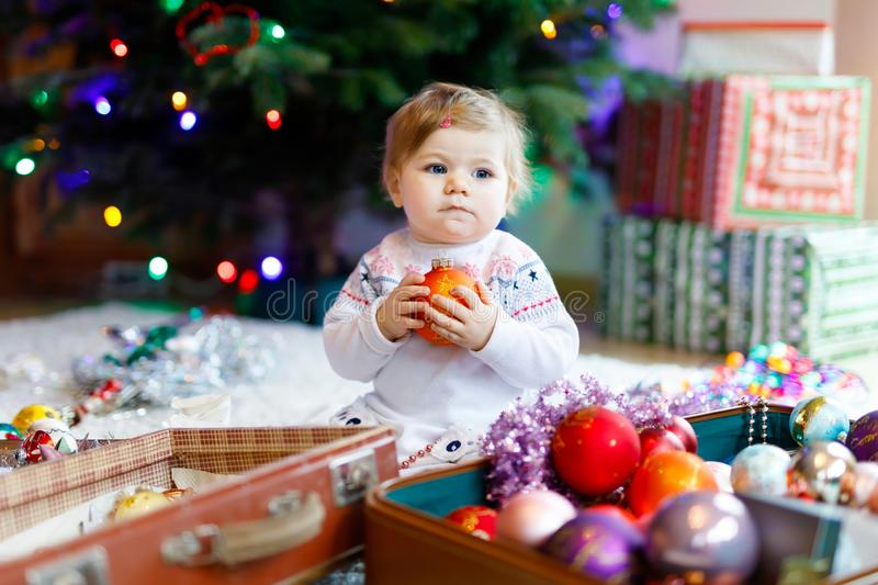 Adorable baby girl holding colorful vintage xmas toys and ball in cute hands. Little child in festive clothes decorating. Adorable baby girl holding colorful royalty free stock photos