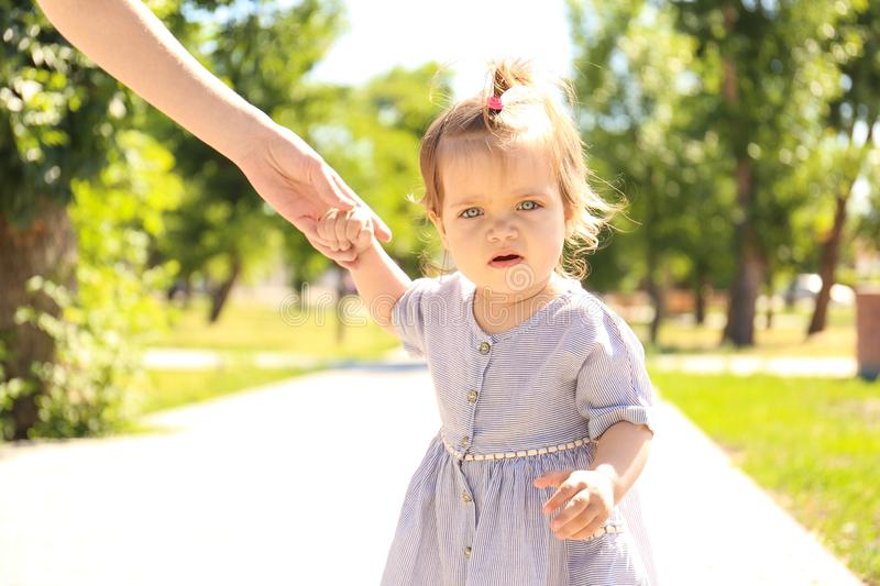 Adorable baby girl holding mother`s hand while learning. To walk outdoors royalty free stock images
