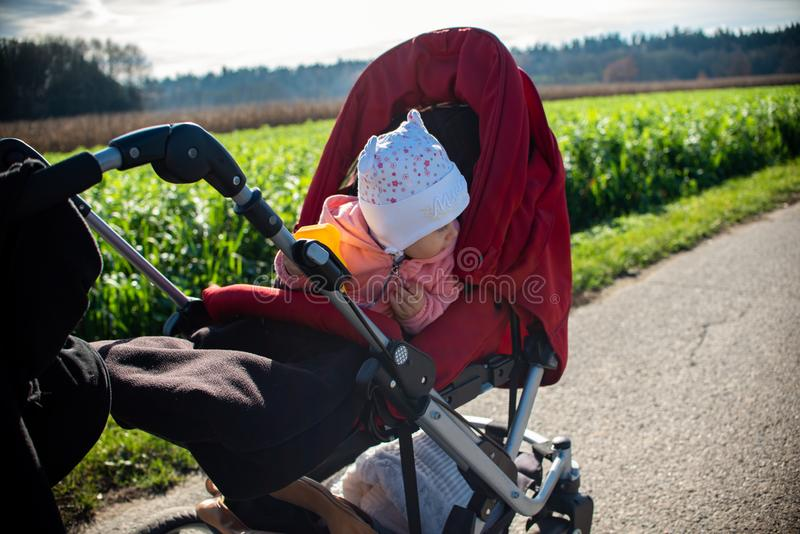 Adorable baby girl outside in red stroller in green fields on a road, royalty free stock image