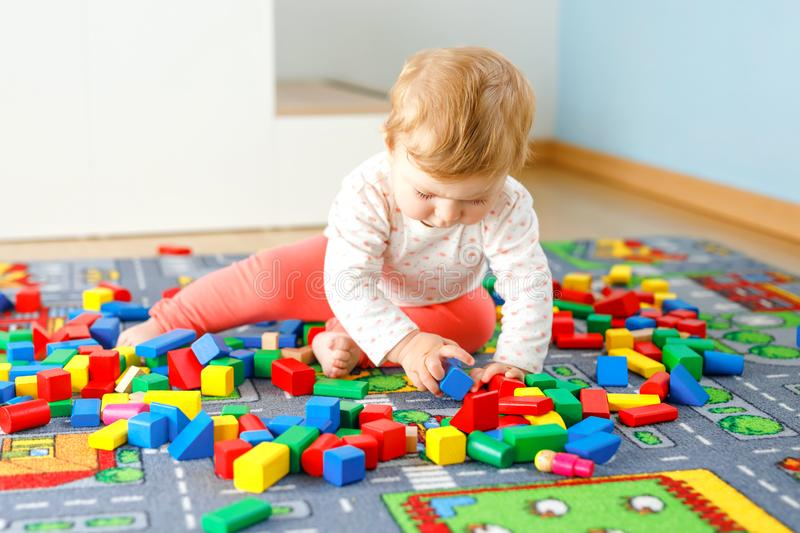 Adorable baby girl playing with educational toys . Happy healthy child having fun with colorful different wooden blocks. At home in domestic room. Baby learning stock photos