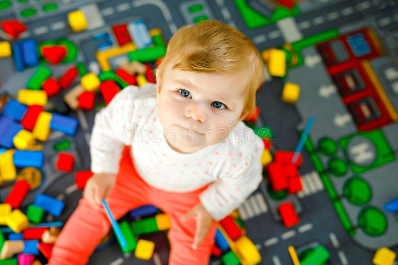 Adorable baby girl playing with educational toys . Happy healthy child having fun with colorful different wooden blocks. At home in domestic room. Baby learning royalty free stock photo