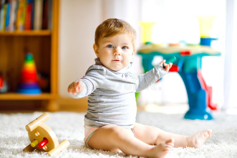 Adorable baby girl playing with educational toys . Happy healthy child having fun with colorful different wooden toy at stock image