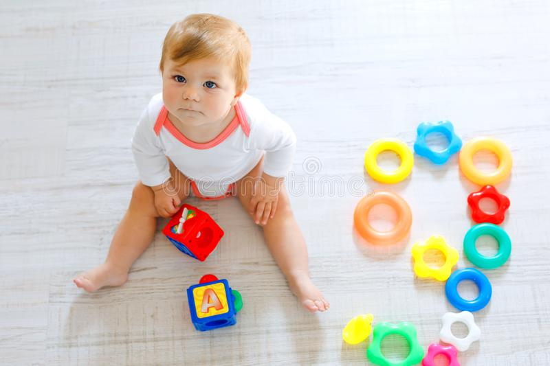 Adorable baby girl playing with educational toys in nursery. Happy healthy child having fun with colorful different toys. At home. Kid trying to build plastic stock image