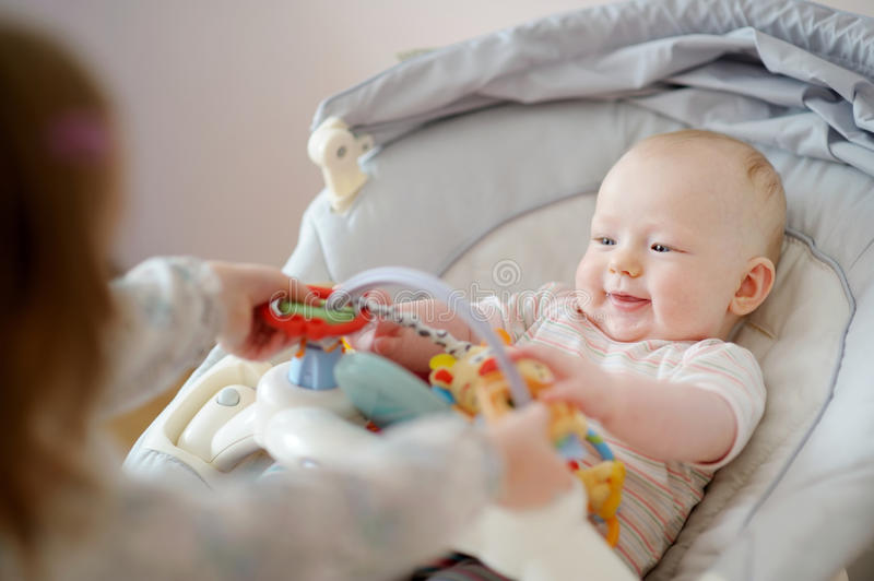 Adorable baby girl playing with older sister. Adorable baby playing with older sister stock photos