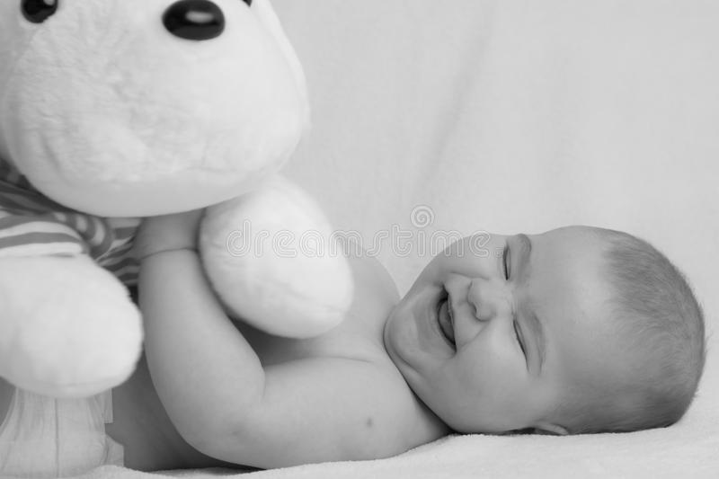 Adorable Baby Girl Playing With A Plush Toy In Black And White. Beautiful Monochrome Photograph Of A Cute Baby Girl Playing With A Plush Toy Lying On Her Back stock photography