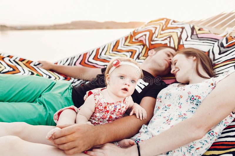 Adorable baby girl  shocked face, lying with her happy father and mother, young hipster couple relaxing with daughter in  a stock photography