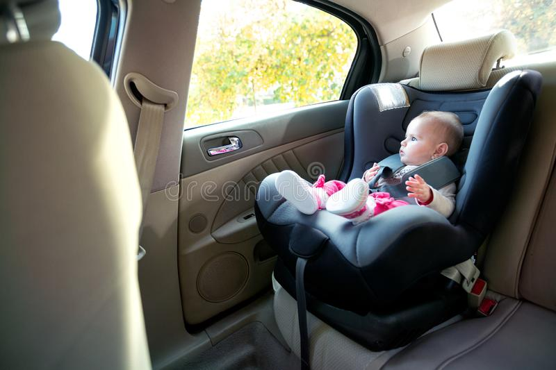 Adorable baby girl sitting and looking outside of a cars window royalty free stock photography