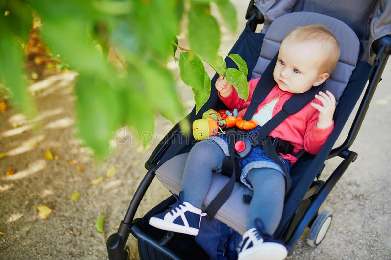 Adorable baby girl sitting in stroller and looking at leaves on a fall or spring day in park. Kids exploring nature royalty free stock images