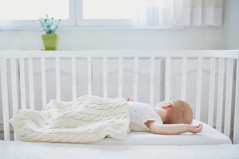 Baby sleeping in co-sleeper crib attached to parents` bed. Adorable baby girl sleeping in co-sleeper crib attached to parents` bed. Little child having a day nap royalty free stock photography