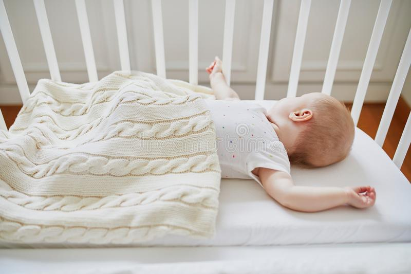Baby sleeping in co-sleeper crib attached to parents` bed. Adorable baby girl sleeping in co-sleeper crib attached to parents` bed. Little child having a day nap stock photos