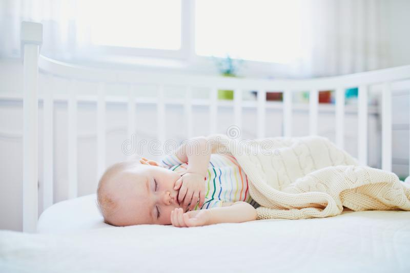 Baby sleeping in co-sleeper crib attached to parents` bed. Adorable baby girl sleeping in co-sleeper crib attached to parents` bed. Little child having a day nap stock photography