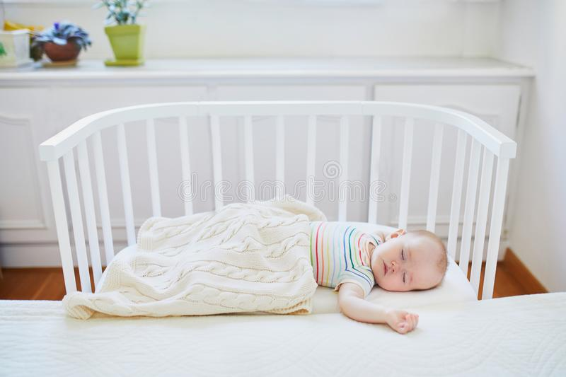 Baby sleeping in co-sleeper crib attached to parents` bed. Adorable baby girl sleeping in co-sleeper crib attached to parents` bed. Little child having a day nap royalty free stock image