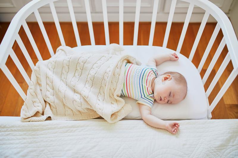 Baby sleeping in co-sleeper crib attached to parents` bed. Adorable baby girl sleeping in co-sleeper crib attached to parents` bed. Little child having a day nap stock image
