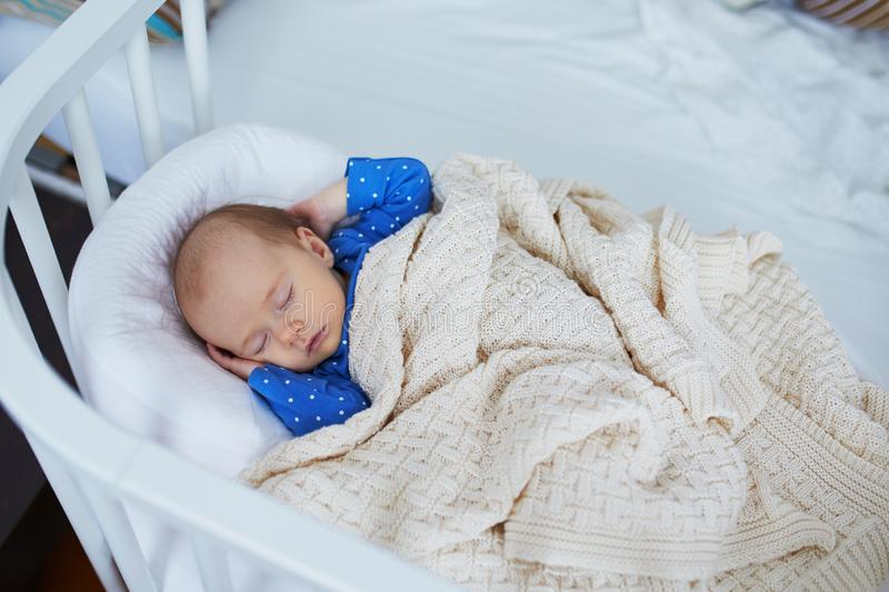 Adorable baby girl sleeping in the crib. Little child having a day nap in cot. Infant kid resting in nursery stock photos