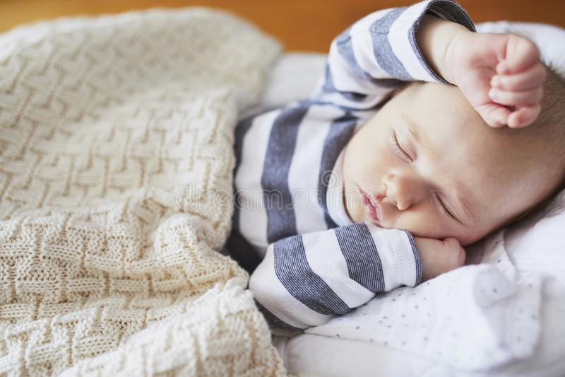 Adorable baby girl sleeping in the crib. Little child having a day nap in cot. Infant kid resting in nursery stock photo